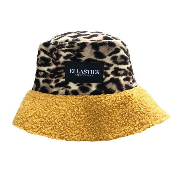 Reversible bucket hat met teddy stof en de kleur geel en panterprint stof en het logo op de voorkant
