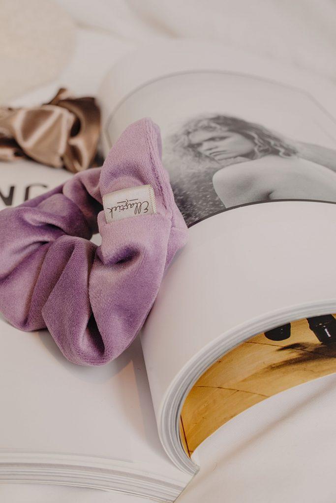 een lila Velvet Scrunchie met luxe uitstraling liggend op een Tijdschrift